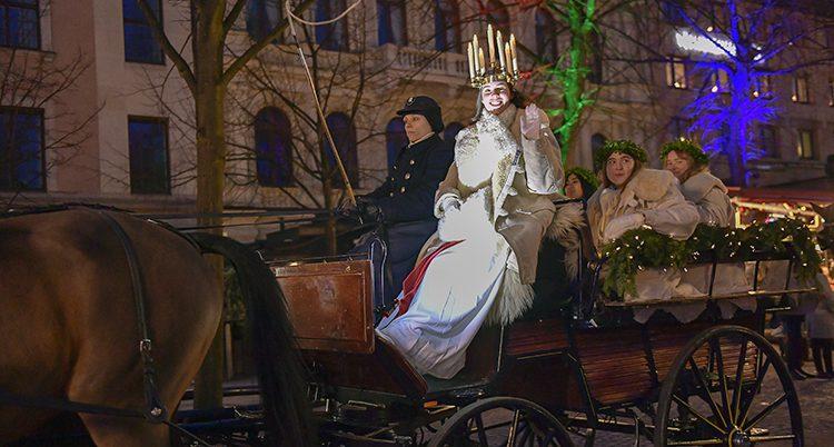 En lucia med tända ljus i en krans i håret sitter i en häst och vagn.