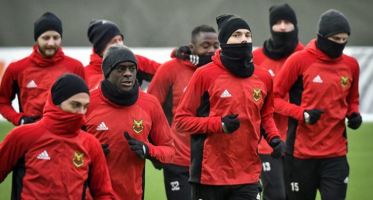 En grupp av spelarna i Östersund värmer upp. De har röda jackor och mössor och halsdukar.