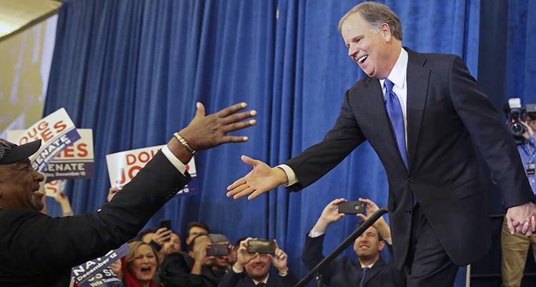 En bilde på politikern Doug Jones som står på ett podium och sträcker ut handen för att hälsa på en supporter. Nedanför står flera personer och jublar och fotar. En av dem sträcker ut sin hand för att hälsa.
