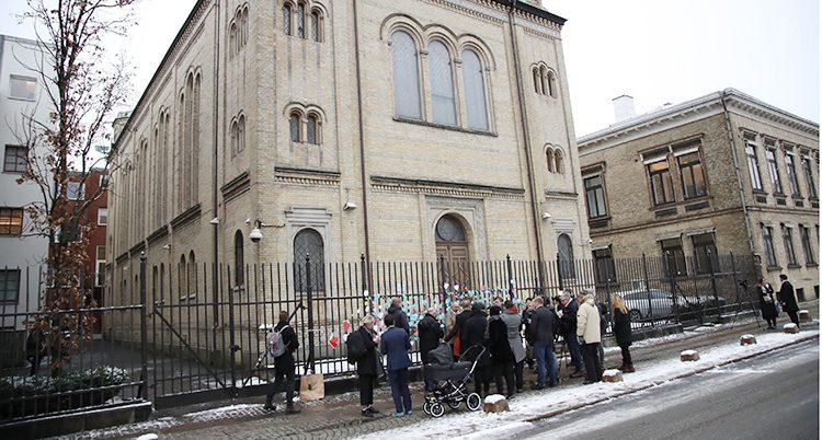 En bild på byggnaden som är synagogan i Göteborg. Utanför staketet står en samling människor och tittar på staketet där det hänger pappershjärtan.
