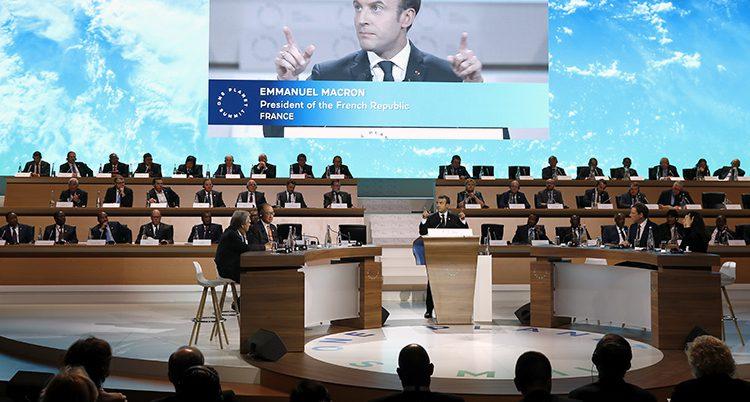 En stor sal med halvmåneformade bänkar. Runt om dem sitter politiker. Vid en pulpet står franska presidenten och håller tal. På en storbildsskärm ovanför syns hans ansikte.