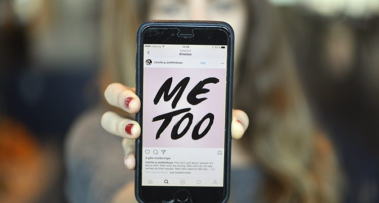 En hand håller upp en mobil som visar texten: Me Too.