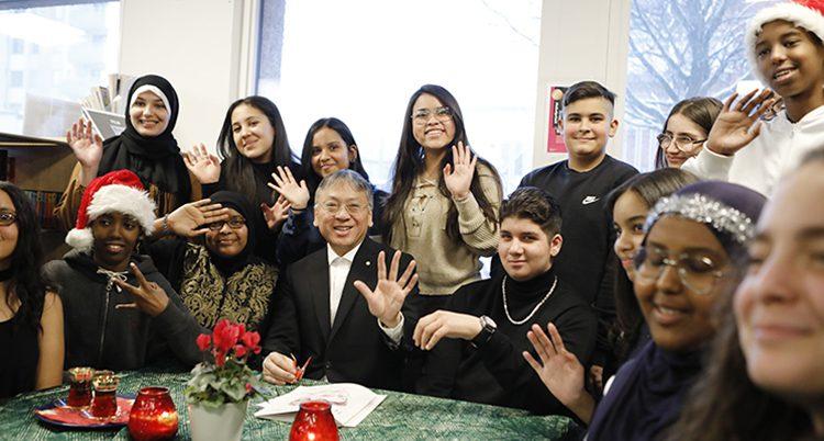 Författaren sitter vid ett bord omringad av elever. Alla vinkar mot kameran.