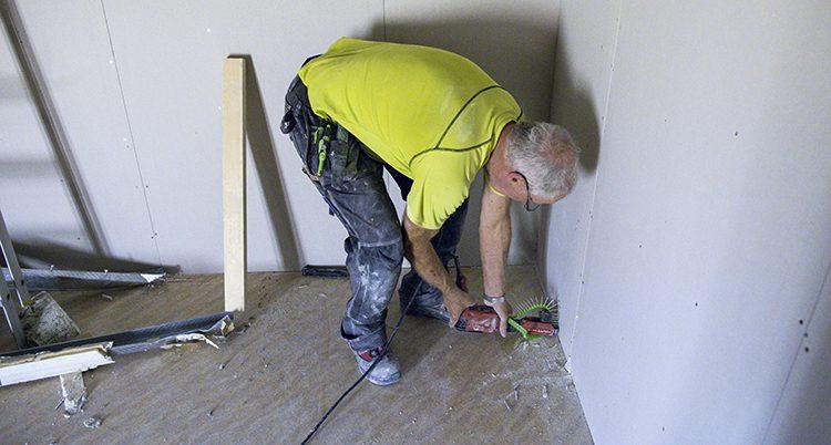 En man jobbar i ett hus.
