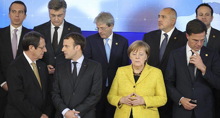 Flera länders ledare poserar för en bild. Alla tittar åt olika håll. Några pratar med varandra. Merkel tittar ner och ser besvärad ut. Bilden är troligen tagen medan politikerna fortfarande håller på att göra sig klara för att bli fotograferade.