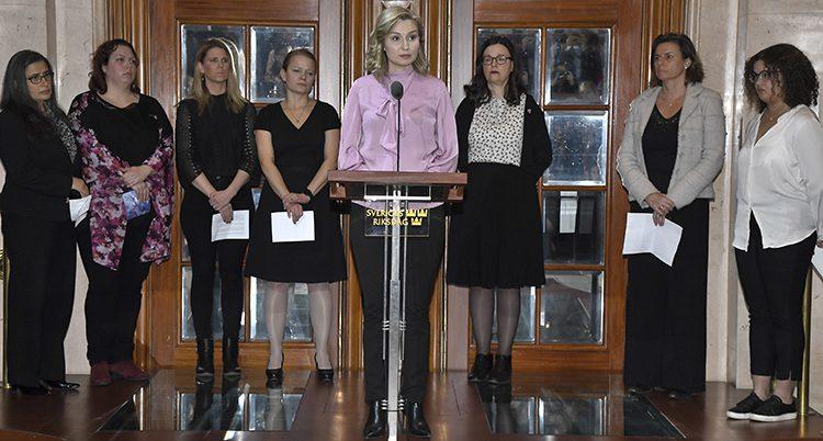 Ebba Bush Thor står vid en pulpet och pratar i en mikrofon. Bakom henne står flera politiker uppradade. De är alla kvinnor och ser allvarliga ut.
