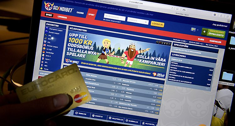 En hand håller ett betalkort framför en sajt för att spela.