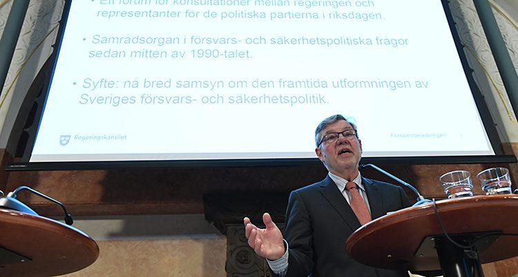 En man med slips framför en stor skärm med text