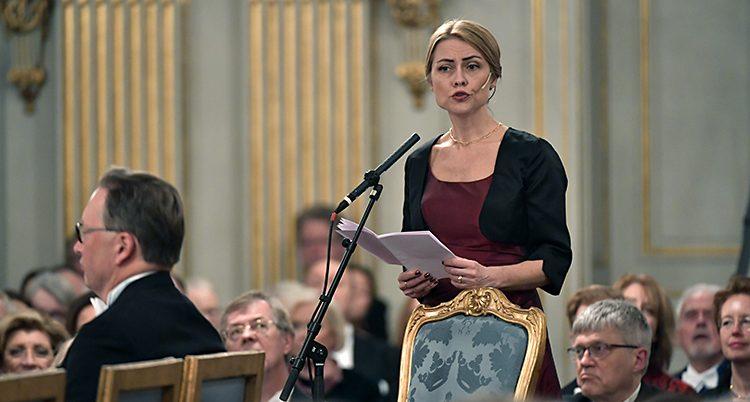 Jayne Svenungsson håller tal. Hon står bakom sin stol och pratar in i en mikrofon. I händerna håller hon ett papper. Stolen har en ram av guld. Den är också klädd i blått tyg.