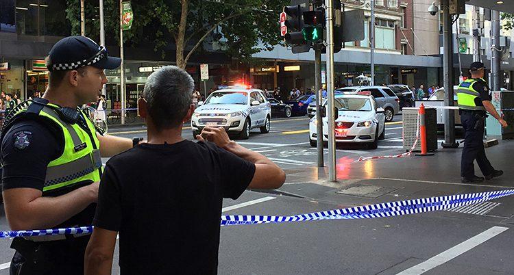 En bild på en gata i Melbourne. Längst fram i bilden syns en polis som pratar med en förbipasserande. Ett band spärrar av gatan mellan dem. Längre bak i bilden syns polisbilar med sirenerna påslagna.