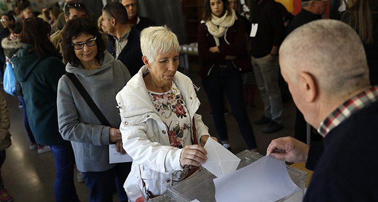 En kvinna i vitt kortklippt hår och vit jacka lägger ner en röst i en låda i Katalonien.