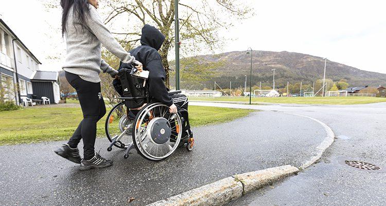 En ung person blir körd i rullstol.