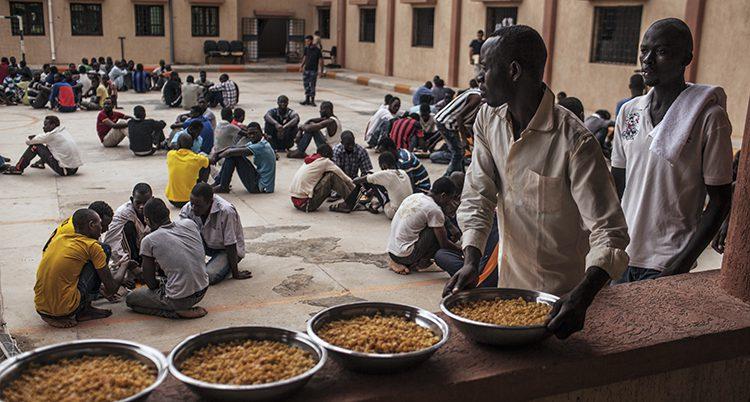 Flyktingar i ett läger i Libyen äter mat på golvet.