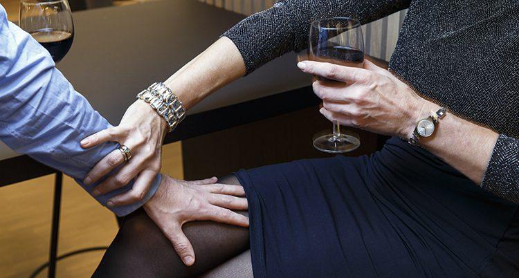 En kvinna tar bort en ovälkommen hand från sitt lår.