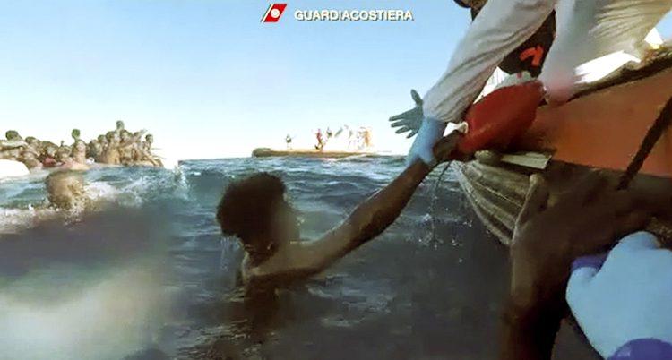 En man i vattnet sträcker sin arm mot en man i en båt.