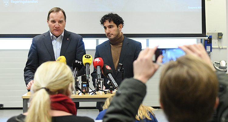 Ministrarna står vid ett bord bakom ett gäng mikrofoner.