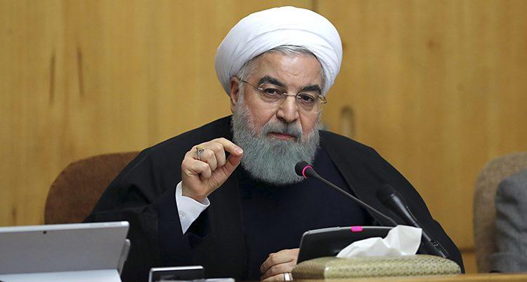 En man med vit turban och grått skägg pratar i mikrofon