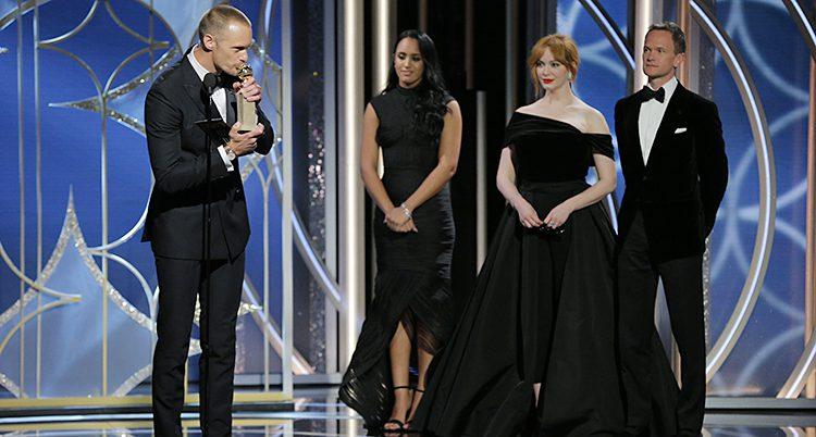 Skarsgård gysser en staty. Bredvid står tre personer i svarta kläder.