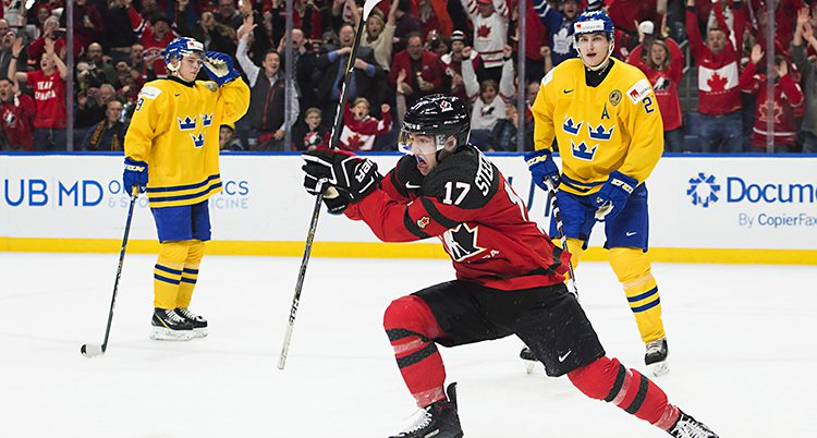Två spelare från Sveriges lag står bakom en glad spelare från Kanada
