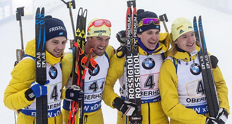 Fyra glada skidåkare i gula overaller