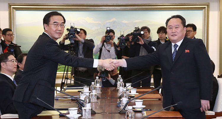Två män i kostym tar i hand över ett bord och tittar in i kameran.