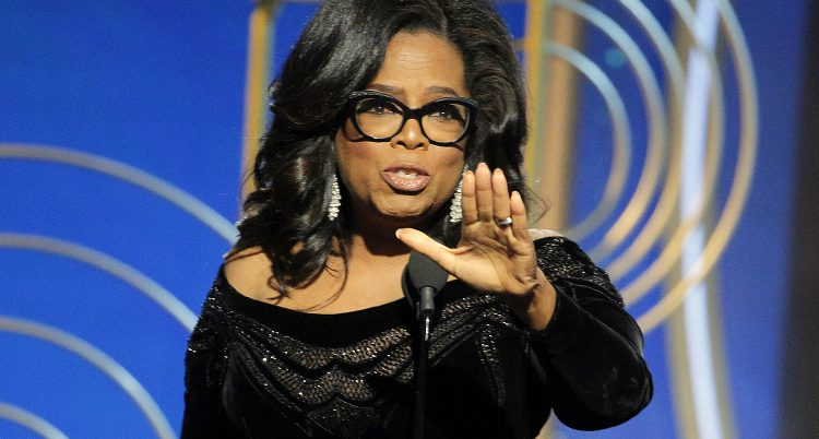 Oprah Winfrey pratar i en mikrofon och håller fram handen.
