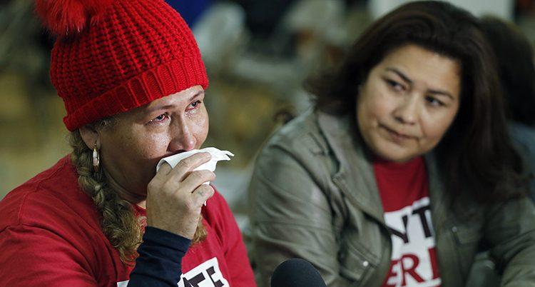 Två kvinnor med ledsna ansikten. En gråter och snyter sig.