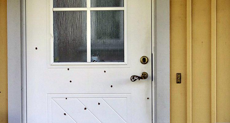 Skotthål i dörren till huset.