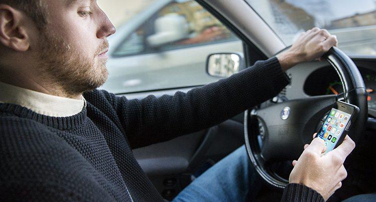 En man pratar i mobilen när han kör