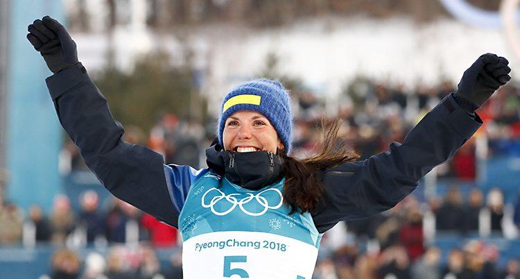 Charlotte Kalla ler och höjer armarna mot luften