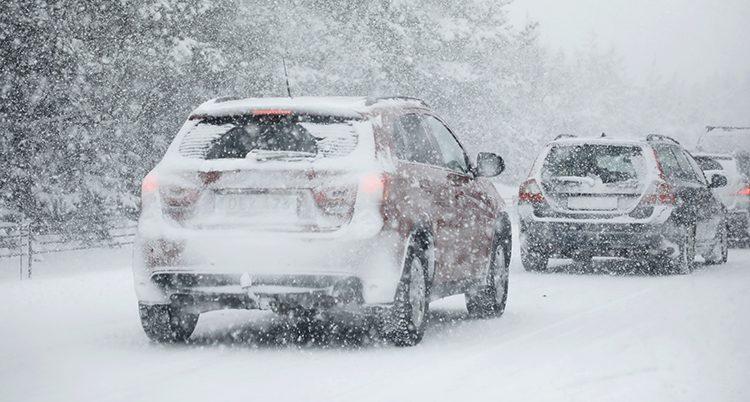 Bilar på väg genom snön.