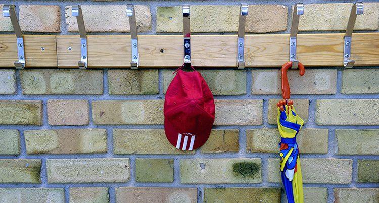 En keps hänger på en krok utanför ett klassrum.