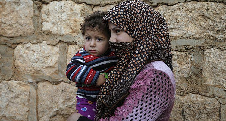 En mamma bär ett litet barn på armen.