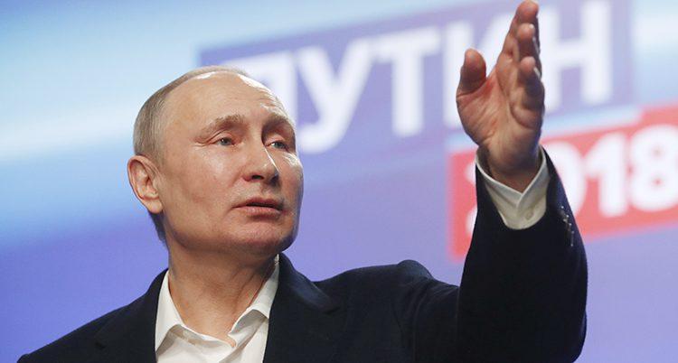 Vladimir Putin står på en scen och pratar. Han pekar med sin hand. Han har en vit skjorta och en mörk kavaj.