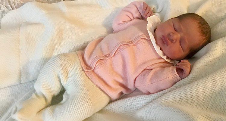 Den nyfödda prinsessan klädd i vita byxor och rosa kofta ligger på en bädd i vitt. Hon blundar.