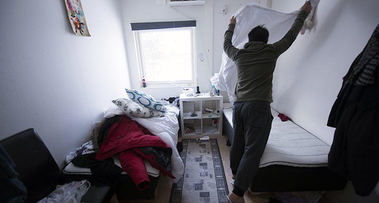 En man bäddar sin säng på ett hem för flyktingar i norra Sverige.