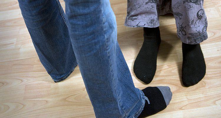 Fötterna på en vuxen bredvid ett barn.