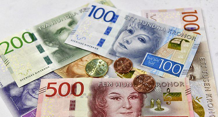En hög med sedlar och mynt.