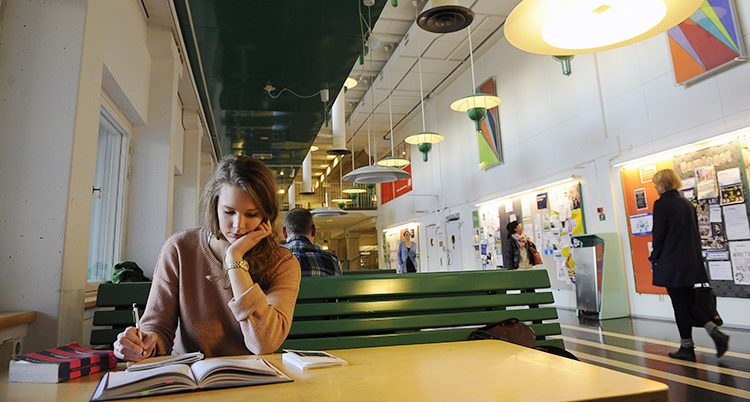 En kvinna sitter vid ett bord och läser en bok.