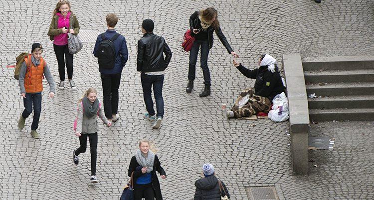 En person sitter på marken och tigger.