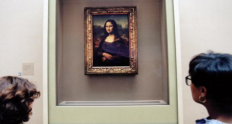 En bild på tavlan Mona-Lisa. Ramen är av guld. Bilden är mörk förutom Mona-Lisas ljusa ansikte och händer som hon har korsat över midjan.