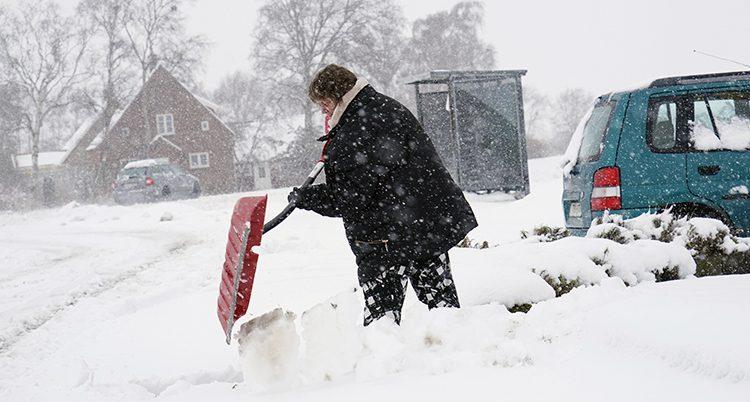 En kvinna skottar snö