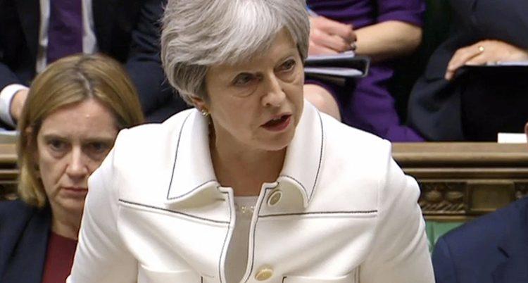 Theresa May i vit klädsel pratar i parlamentet.