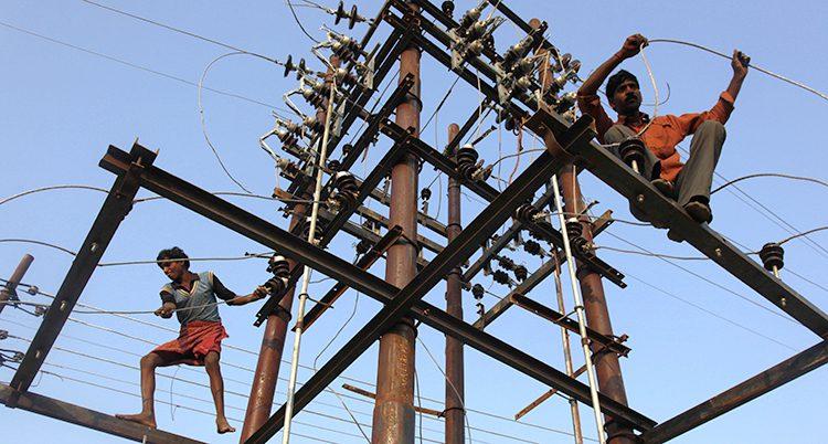 Några män lagar en ledning med el i Indien.