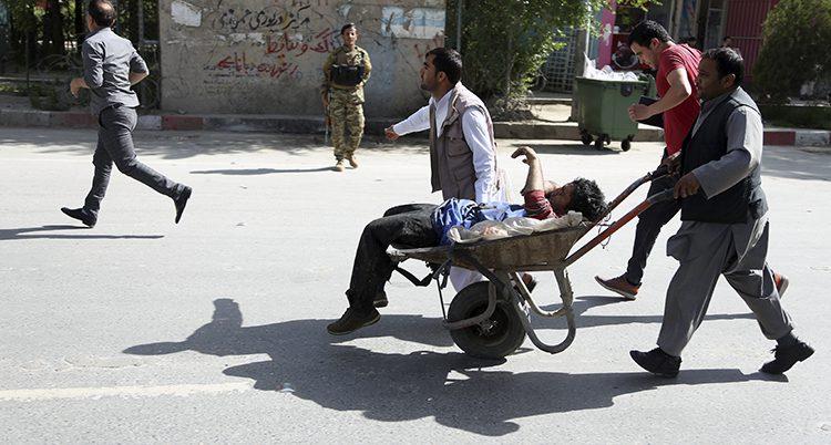 Flera personer kör en skottkärra med en skadad man på en gata i Kabul.