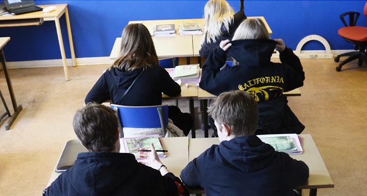 Elever syns sitta vid sina bänkar i ett klassrum.