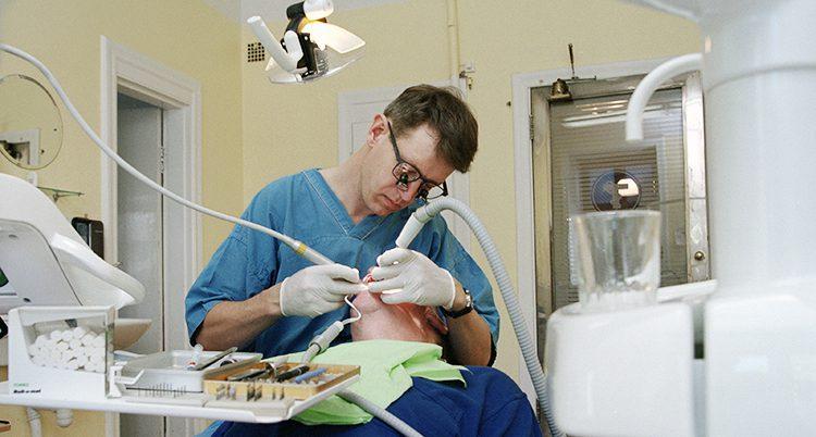 En tandläkare borrar en patient.