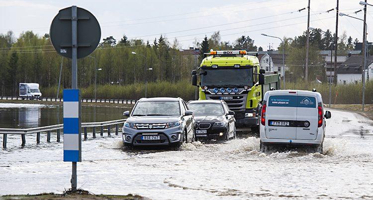 bilar försöker köra över en översvämmad väg.