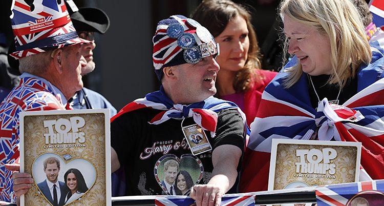 Människor klädda i mössor och skynken av Storbritanniens flagga står vid ett staket. De har bilder på prinsparet.