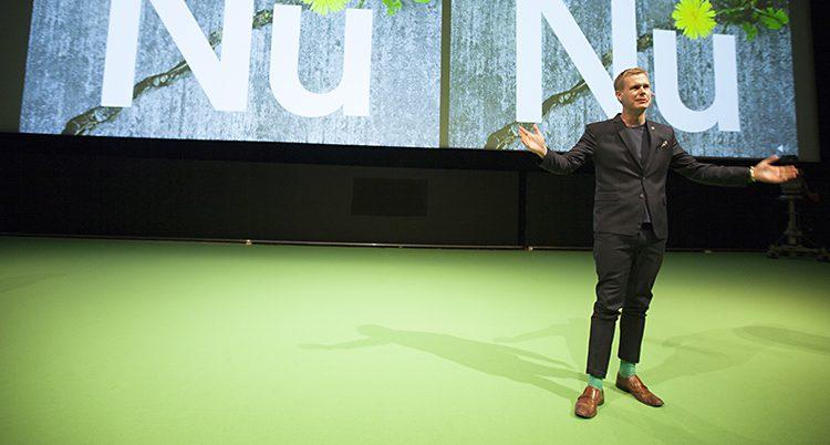 Gustav Fridolin står på scenen på mötet. Han håller ut armarna och pratar till publiken. Han står på en gräsgrön matta.